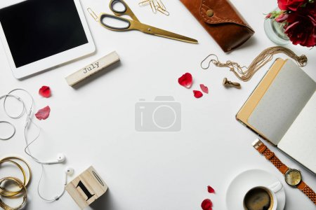 Foto de Top view of digital tablet, jewelry, earphones, case, flowers, office supplies and coffee on white surface - Imagen libre de derechos