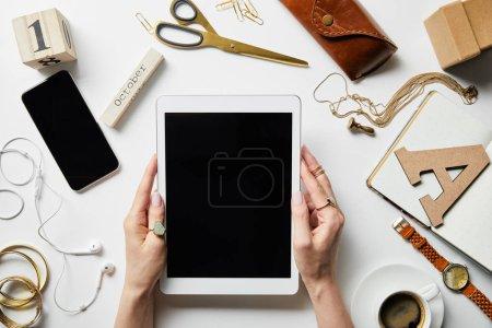 Foto de Vista recortada de la mujer sosteniendo la tableta digital en las manos cerca del teléfono inteligente, auriculares, joyas, caja, flores, artículos de oficina y café en la superficie blanca - Imagen libre de derechos