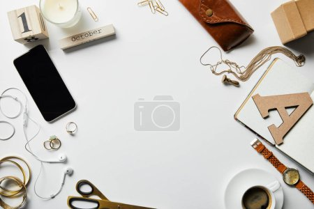 Foto de Top view of smartphone, notepad, candle, case, earphones, plants, office supplies and coffee with jewelry on white surface - Imagen libre de derechos