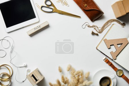 Photo for Top view of smartphone, notepad, case, earphones, plants, office supplies and coffee with jewelry on white surface - Royalty Free Image
