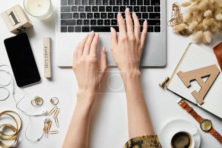 Foto de Vista recortada de la mujer que trabaja con la computadora portátil en la superficie blanca con papelería, plantas, joyas, café y bloc de notas - Imagen libre de derechos