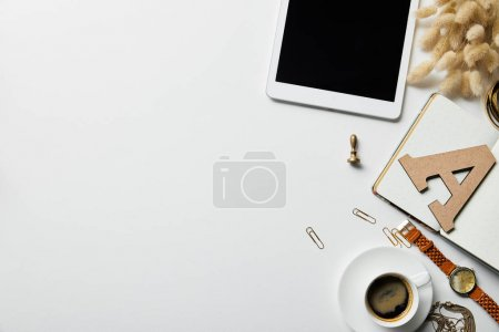 Photo for Top view of digital tablet, stationery, coffee, watch and notebook on white surface - Royalty Free Image