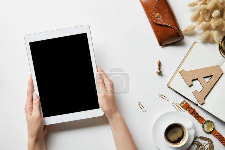 Photo pour Vue recadrée de la tablette numérique dans les mains de la femme sur la surface blanche avec papeterie, bijoux, bloc-notes, étui et café - image libre de droit