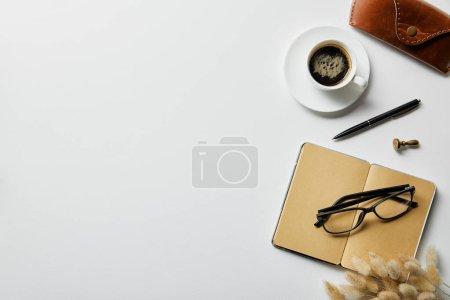 Photo pour Vue du dessus du café, bloc-notes avec stylo et étui sur la surface blanche - image libre de droit