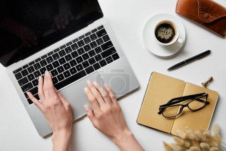 Photo pour Vue recadrée de la femme travaillant avec un ordinateur portable près de lunettes, café, étui et bloc-notes sur la surface blanche - image libre de droit