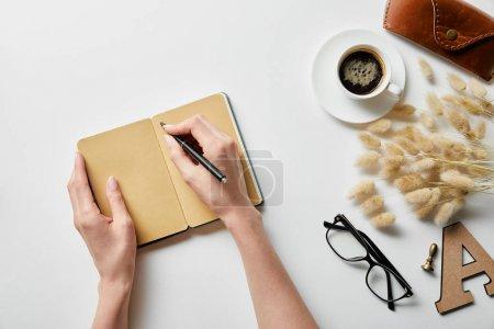 Photo pour Vue recadrée de la femme écrivant dans un bloc-notes près du café, des lunettes et du boîtier sur une surface blanche - image libre de droit