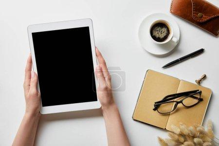 Photo pour Vue recadrée de la femme tenant tablette numérique dans les mains près de bloc-notes, café, lunettes et étui sur la surface blanche - image libre de droit