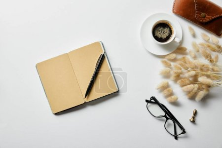 Photo for Top view of notepad with pen, coffee, glasses and case on white surface - Royalty Free Image