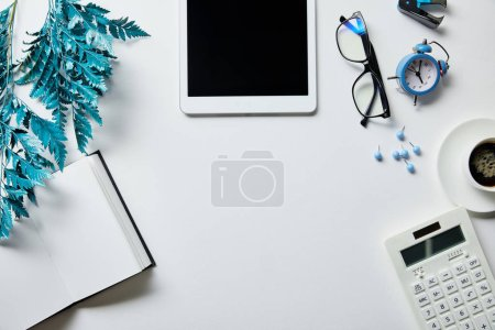 Photo for Top view of notepad, digital tablet, coffee, stationery, alarm clock, calculator, glasses and blue branch on white surface - Royalty Free Image
