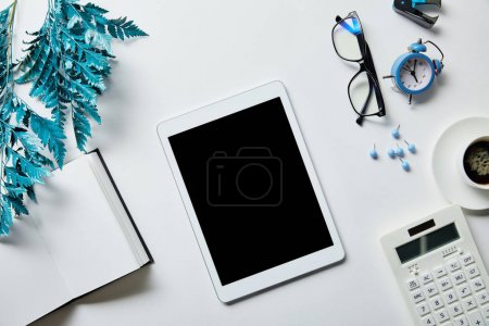Photo for Top view of digital tablet near notepad, coffee, stationery, alarm clock, calculator, glasses and blue branch on white surface - Royalty Free Image
