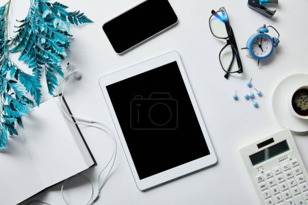 Photo for Top view of digital tablet, smartphone, notepad, earphones, coffee, stationery, alarm clock, calculator, glasses and blue branch on white surface - Royalty Free Image