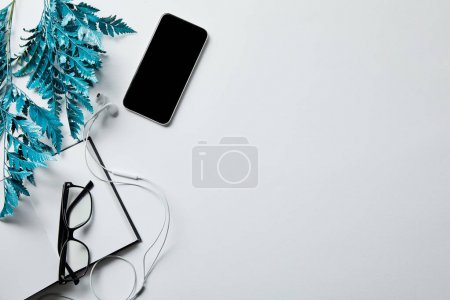 Photo for Top view of smartphone near notepad, glasses and blue branch on white surface - Royalty Free Image