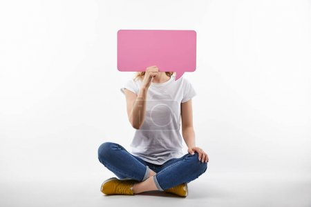 Foto de Woman with pink speech bubble in hands sitting isolated on white - Imagen libre de derechos