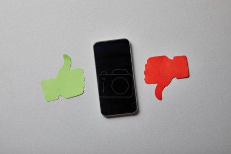 Photo pour Smartphone près du pouce vers le haut et du pouce vers le bas le signe de papier sur la surface blanche - image libre de droit