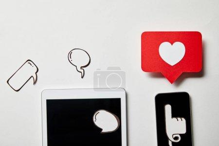tablette numérique et smartphone avec pensée papier et bulles vocales, coeur en papier, carte de pointage sur surface blanche