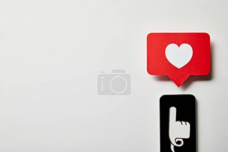Photo for Smartphone with pointing and like sign card on white surface - Royalty Free Image