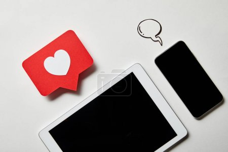 Photo for Smartphone near digital tablet with like sign card and paper speech bubble on white surface - Royalty Free Image