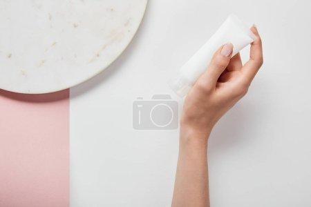 Photo pour Vue recadrée de femme retenant le tube de crème près de la plaque sur la surface rose blanche - image libre de droit