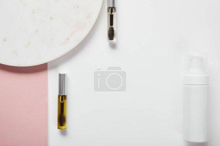 Photo pour Vue de dessus des bouteilles de mascara et du distributeur de cosmétiques près de la plaque sur la surface rose blanche - image libre de droit