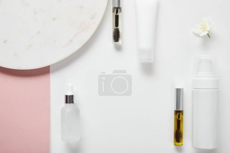 Photo for Top view of mascara and glass bottles, cream tube, cosmetic dispenser near plate, jasmine on white pink surface - Royalty Free Image