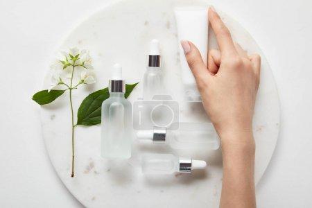 Photo pour Vue recadrée de la main de la femme avec tube à crème sur plaque avec du jasmin et des bouteilles en verre cosmétique sur surface blanche - image libre de droit