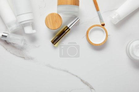 Photo for Cropped view of cream tubes, cosmetics jars, dispenser and glass bottle with eye brush on white surface - Royalty Free Image