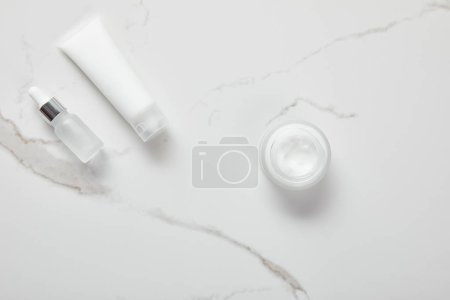 Photo for Top view of cosmetic glass bottle, jar with cream and moisturizer tube on white surface - Royalty Free Image