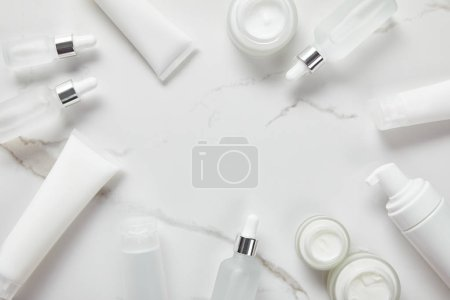 Photo for Top view of cosmetic glass bottles, jar with cream, moisturizer tubes, dispenser and jasmine on white surface - Royalty Free Image