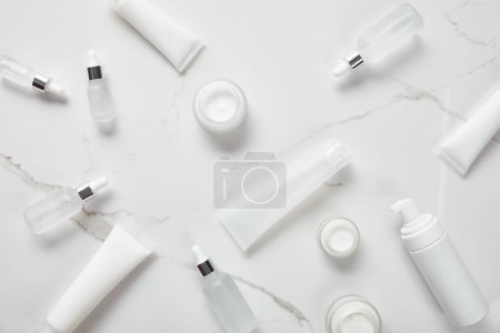 top view of cosmetic glass bottles, jars with cream, moisturizer tubes, dispenser and jasmine on white surface