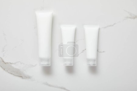 Photo for Top view of cosmetic cream tubes on white surface - Royalty Free Image