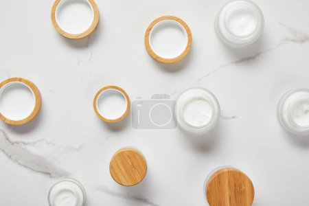 Photo for Top view of jars with cosmetic cream on white surface - Royalty Free Image