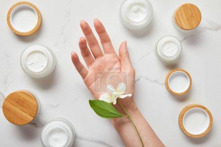 Photo pour Vue recadrée des fleurs de jasmin sur la main de la femme près des bocaux avec crème cosmétique sur la surface blanche - image libre de droit