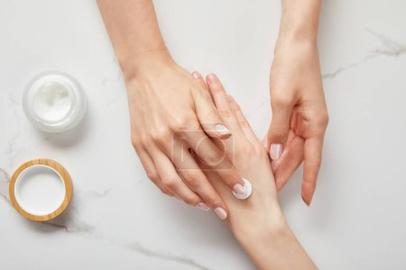 Photo for Cropped view of woman applying cream on hand, using white moisturizer from jar on white surface - Royalty Free Image