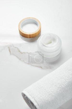 Photo pour Pot ouvert avec la crème cosmétique et le chapeau en bois près de la serviette sur la surface blanche - image libre de droit