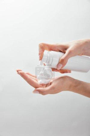 Photo pour Vue recadrée de femme utilisant le distributeur cosmétique avec la mousse d'isolement sur le blanc - image libre de droit