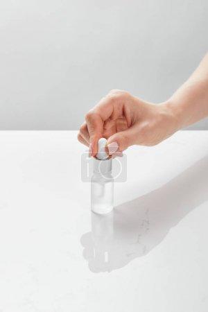 Photo pour Vue recadrée de la main de femme avec la bouteille en verre cosmétique - image libre de droit
