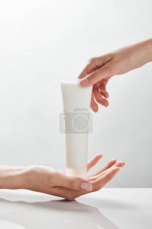 Photo pour Vue recadrée des mains de femme retenant la crème cosmétique dans le tube - image libre de droit