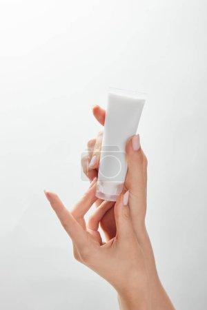 Photo pour Vue recadrée de la femme tenant tube de crème cosmétique dans les mains isolées sur blanc - image libre de droit