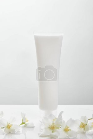 Photo for Jasmine flowers on white surface near cosmetic cream in tube - Royalty Free Image
