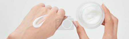 Photo pour Tir panoramique de la femme appliquant la crème sur la peau et retenant le pot d'isolement sur le blanc - image libre de droit