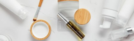 Photo for Panoramic shot of cream tubes, cosmetics jars, dispenser, glass and mascara bottles with eye brush on white surface - Royalty Free Image