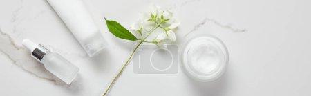 Photo pour Coup panoramique de jasmin, bouteille en verre cosmétique, pot à la crème et tube hydratant sur surface blanche - image libre de droit