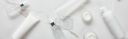 Photo pour Prise panoramique de bouteilles en verre cosmétiques, pots à la crème, tubes hydratants et distributeur sur surface blanche - image libre de droit