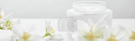 Photo pour Plan panoramique de fleurs de jasmin sur la surface blanche près du bocal avec crème - image libre de droit