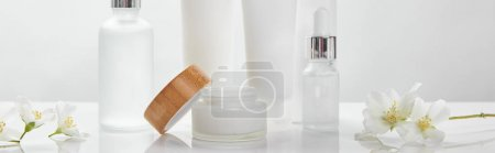 Photo for Panoramic shot of cream in tubes, jar and cosmetic glass bottles with jasmine on white surface - Royalty Free Image