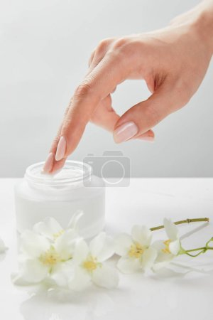 cropped view of woman hand touching cream in jar near jasmine flowers on white surface