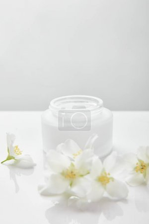 Photo for Jasmine flowers on white surface near jar with cream - Royalty Free Image