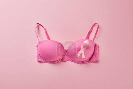 Photo pour Vue du dessus du ruban sur le soutien-gorge sur fond rose, concept de cancer du sein - image libre de droit