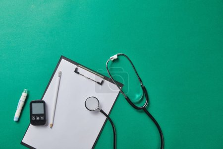 Photo for Top view of blood lancet and stethoscope near glucometer and pencil on folder on green background - Royalty Free Image