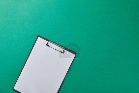 Photo for Top view of folder with empty paper isolated on green - Royalty Free Image